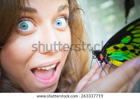 delight of girl, holding a butterfly on a hand - stock photo