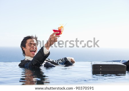 Delighted businessman relaxing in a swimming pool with a cocktail in a suit - stock photo