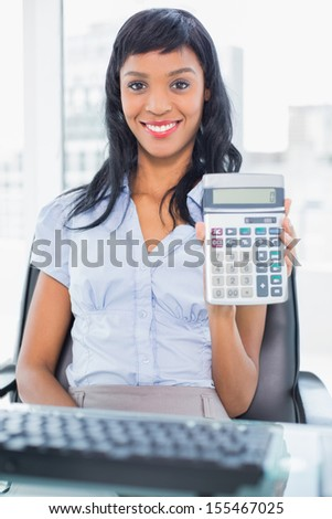 Delighted businesswoman holding a calculator in office - stock photo