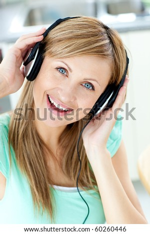 Delighted caucasian woman listening to music with headphones in the kitchen at home