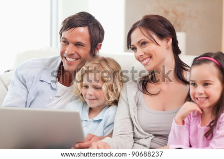 Delighted family using a notebook in a living room - stock photo