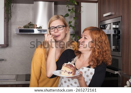 Delighted girlfriends enjoying cake and feeding each other in the kitchen at home. - stock photo