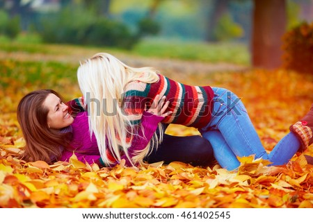 delighted girls, friends having fun among fallen leaves in autumn park