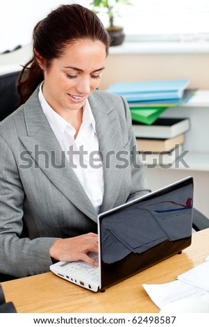 Delighted hispanic businesswoman working at her laptop in her office