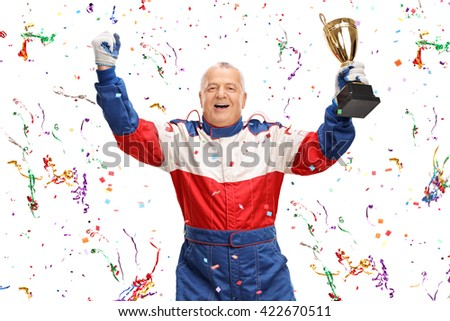 Delighted mature car racing champion holding a trophy and celebrating with confetti streamers around him  - stock photo