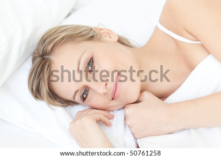 Delighted relaxed woman lying on her bed at home