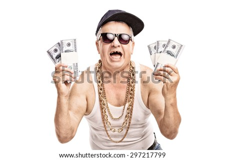 Delighted senior in hip hop outfit holding a few stacks of money and looking at the camera isolated on white background - stock photo