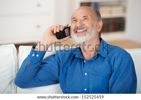 Delighted senior man chatting on a mobile phone while relaxing on a sofa in his living room, natural close up portrait - stock photo