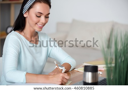 Delighted smiling woman making notes