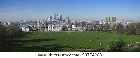 Delighted to present you a panorama taken in Greenwich park with a view on National Maritime Museum, Canary Wharf island skyline and Queen's House with lots of people enjoying sunny spring day. - stock photo