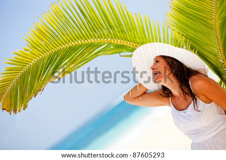 Delighted woman at the beach enjoying her holidays and smiling - stock photo