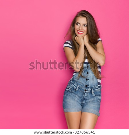 Delighted Woman Looking At Copy Space. Three quarter length studio shot on pink background. - stock photo