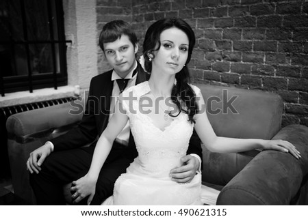 Delightful bride sits before the groom on the couch