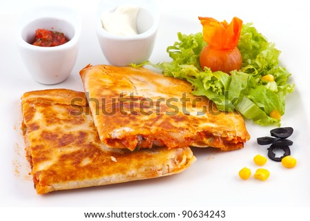 Delightful dish of a Mexican cuisine kesaldia with sauce and vegetables - stock photo