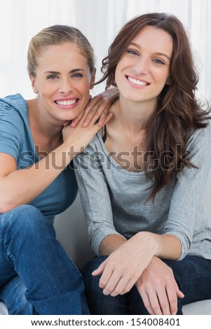 Delightful friends posing while sitting on the couch looking at camera - stock photo