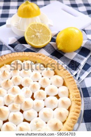 Delightful lemon meringue pie with fresh lemons ready to serve. - stock photo