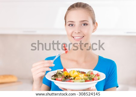 Delightful meal. Nice cheerful charming girl holding fork and eating salad while expressing gladness. - stock photo