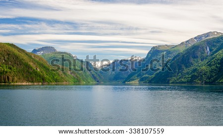 Delightful panoramic sea landscape with blue surface of the water, magic feather clouds on the sky over mountain slopes with green forest and mountain peaks with snow caps in the background, Norway