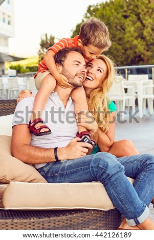 Delightful smiling young woman and happy man sitting and with cute little boy in hotel lobby - stock photo