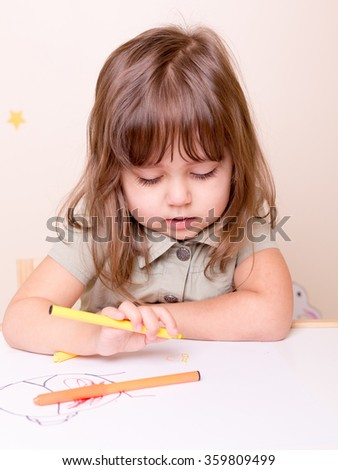 delighting drawing girl at the desk in preschool - stock photo