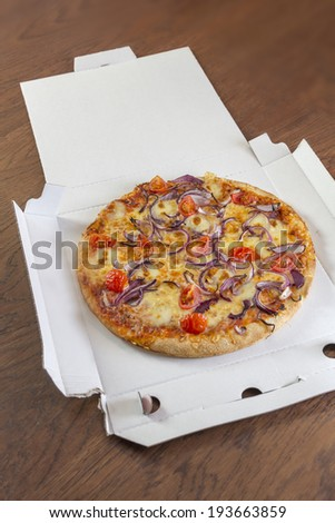 Delivered pizza with tomatoes and onions in a open pizza box on a brown wooden table