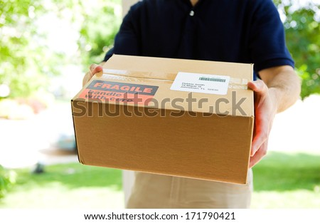 Delivery: Anonymous Delivery Man With Package - stock photo