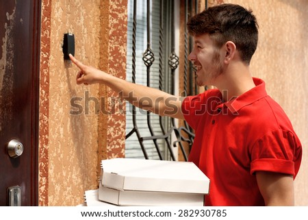 Delivery boy with cardboard pizza box near house of customer, outdoors - stock photo
