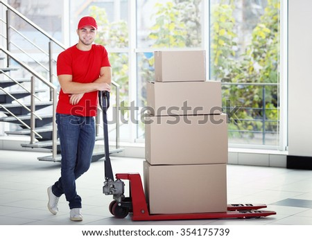 Delivery concept - postman in red uniform with parcels on dolly - stock photo