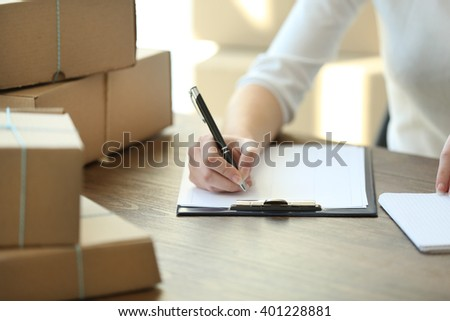 Delivery concept. Woman signs papers among parcels, close up - stock photo
