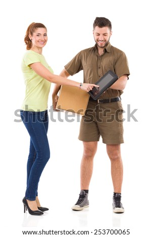 Delivery confirmation. Woman receives a package and pointing at courier's digital tablet. Full length studio shot isolated on white. - stock photo