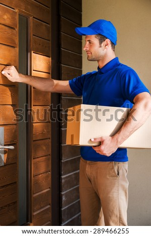 Delivery direct to your door. Handsome young delivery man holding a cardboard box while knocking at the door of house  - stock photo