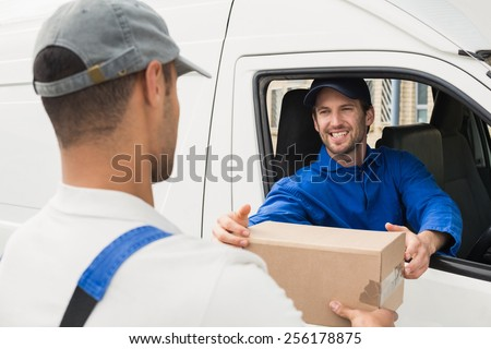 Delivery driver handing parcel to customer in his van outside the warehouse - stock photo