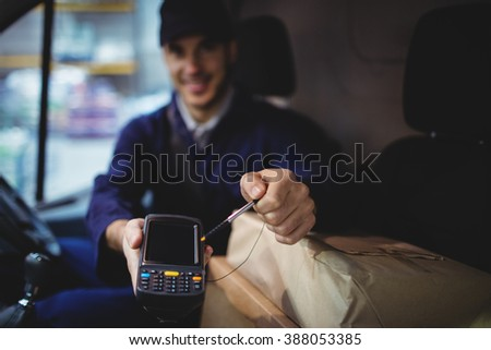 Delivery driver holding device to camera with parcels on seat - stock photo