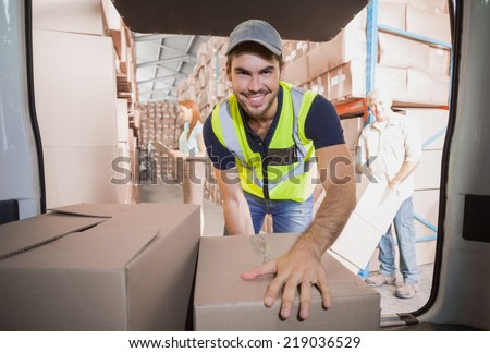 Delivery driver loading his van with boxes outside the warehouse - stock photo