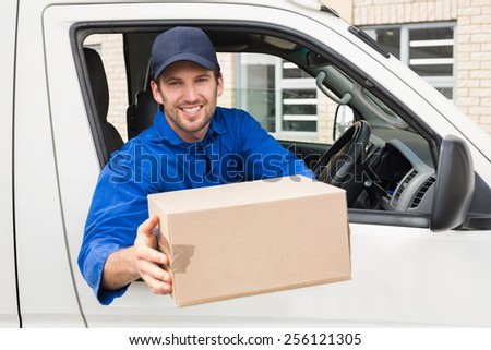 Delivery driver offering parcel from his van outside the warehouse - stock photo
