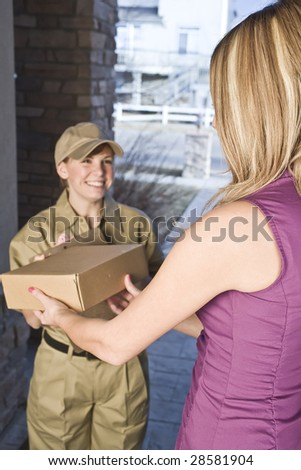 Delivery driver or courier handing package over to a woman - stock photo