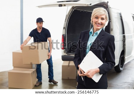 Delivery driver packing his van with manager smiling at camera - stock photo