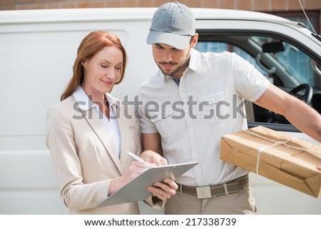 Delivery driver showing where to sign to customer outside the warehouse - stock photo