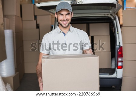 Delivery driver smiling at camera holding box in a large warehouse - stock photo