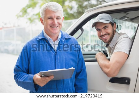 Delivery driver smiling at camera with customer outside the warehouse - stock photo