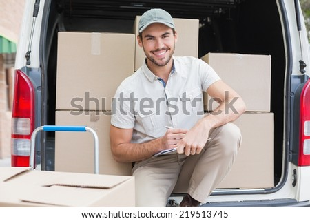 Delivery driver writing in clipboard outside the warehouse - stock photo