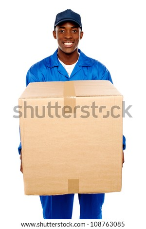 Delivery guy holding big parcel and smiling isolated on white - stock photo
