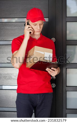Delivery guy with parcel calling a customer - stock photo