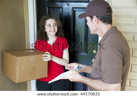 Delivery man brings a package to a customer's door and waits for a signature. - stock photo