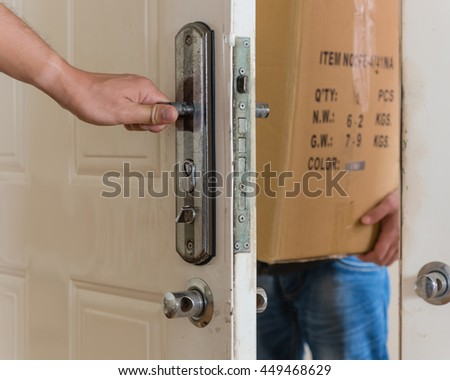 Delivery man brings package to customer front door.