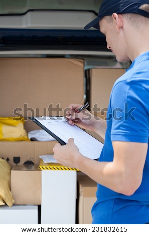Delivery man does paperwork in front of his van - stock photo