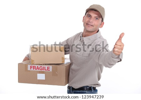 Delivery man giving the thumb's up - stock photo
