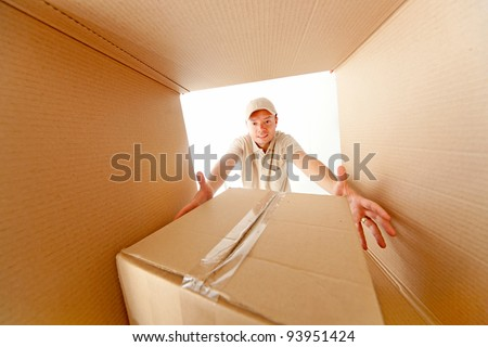Delivery man grabbing a package from inside a mailbox - stock photo