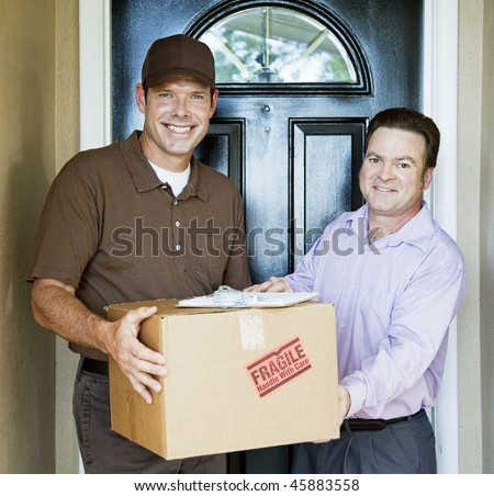 Delivery man hands package to satisfied customer. - stock photo