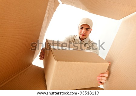 Delivery man holding a package inside a cardboard box - stock photo